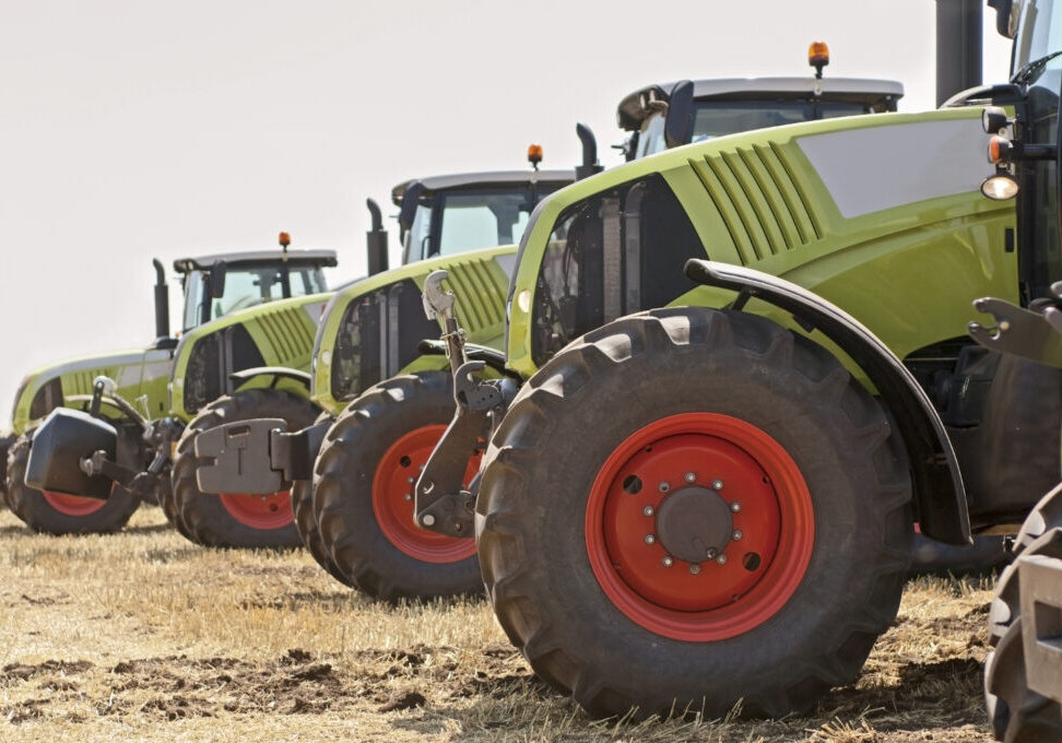 New tractors on field in a row. Selective focus, side view.