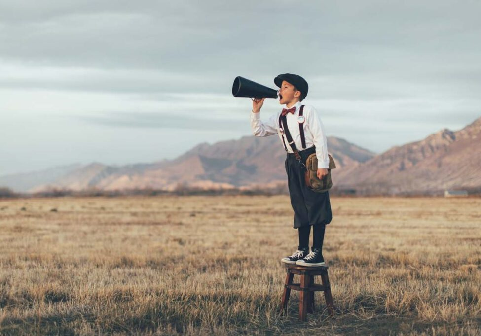 A news boy dressed in vintage knickers and newsboy hat stands yelling through a megaphone in the middle of a field in Utah, USA. He is trying to sell you what your business needs.